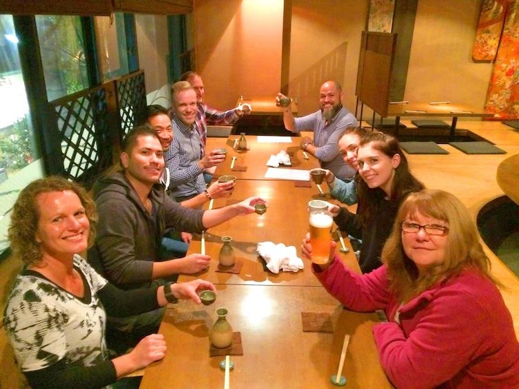 Show item 4 of 10. Group having dinner at a Japanese restaurant