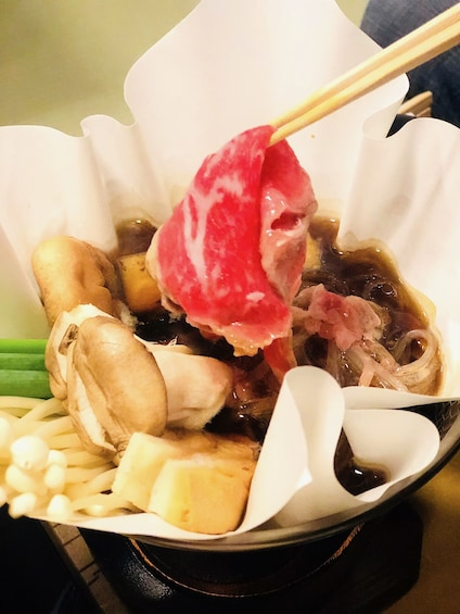 Chopsticks holding meat in a bowl of Japanese food