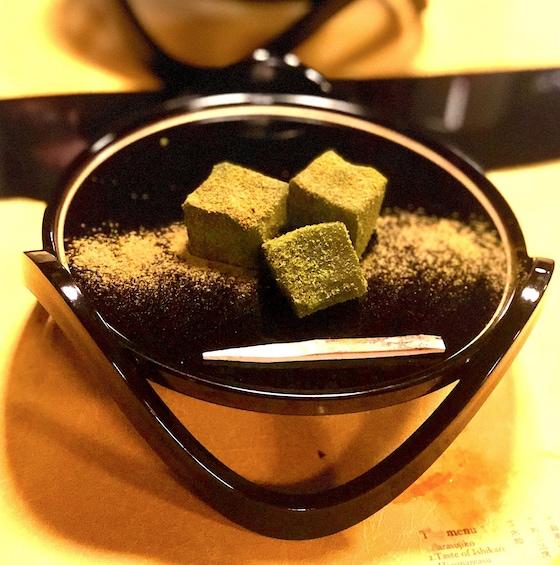 Three green cubes seasoned with salt on a black plate
