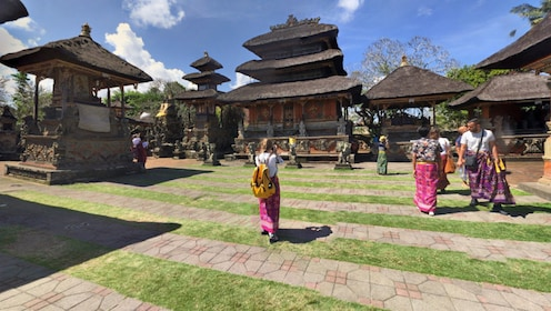 Tourists look at huts in a village in Bali