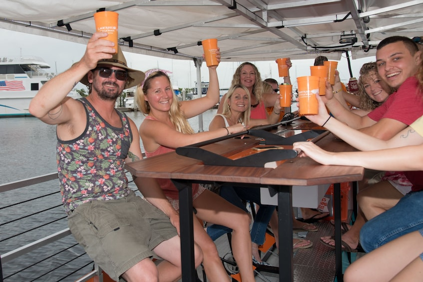 Show item 4 of 4. Cycleboat passengers holding up their drinks in Florida