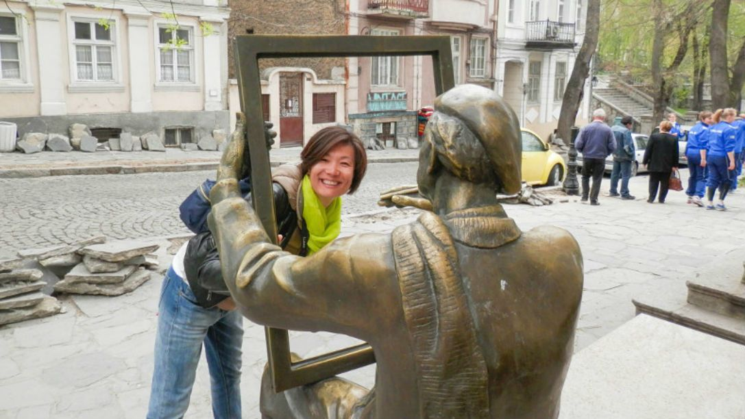 Woman taking a photo with a statue in Plovdiv