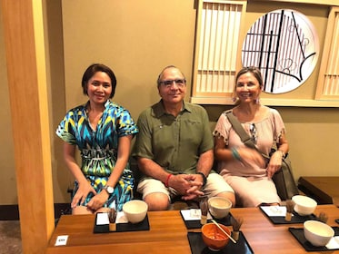Three people sit at a table drinking tea