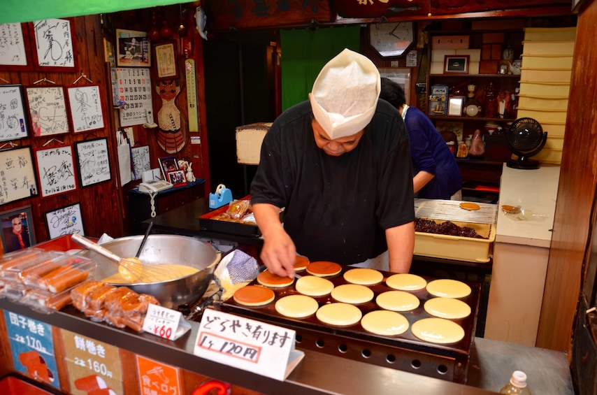 Show item 5 of 8. Chef making hotcakes at a food stand in the Osaka Market