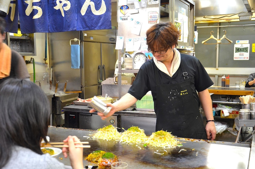 Show item 3 of 8. Person operates a grill at a market in Osaka