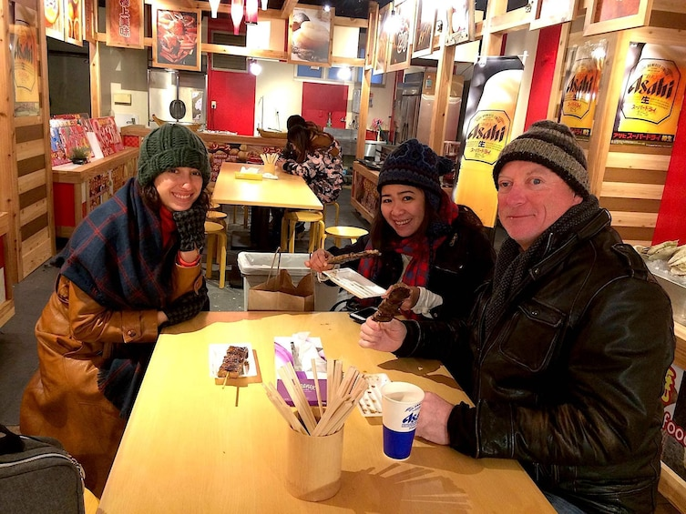 Show item 2 of 8. Three people at a table waiting for food at the Osaka Market