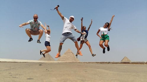 Tour group jumping for joy with pyramids in the background in Egypt