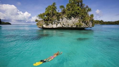 Woman swimming near a rock island in Buzios