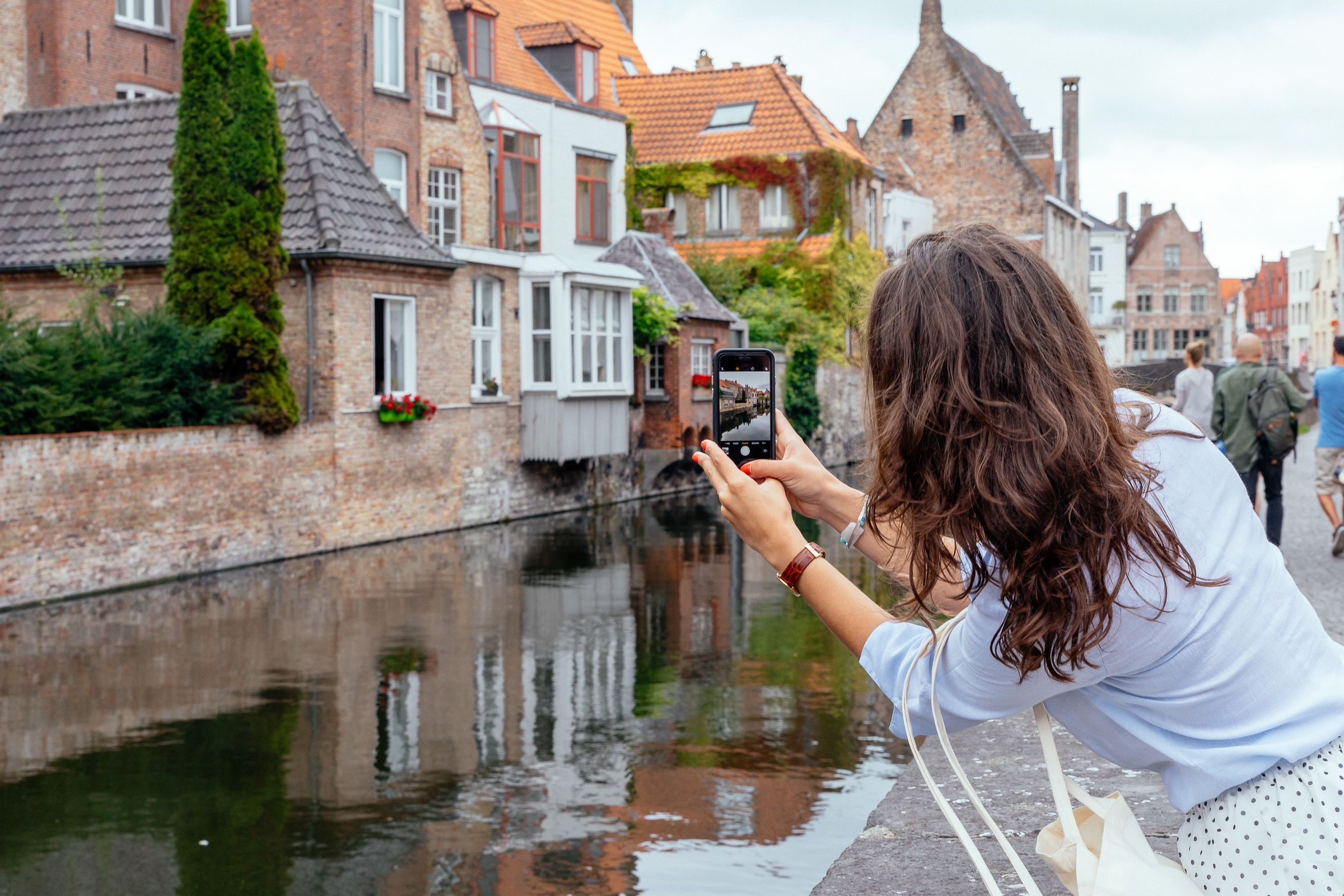 Woman taking a photo with her mobile phone in Bruges