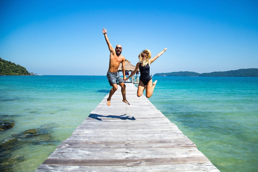 Show item 2 of 5. Couple jumping for joy on a pier over the water in Sihanoukville