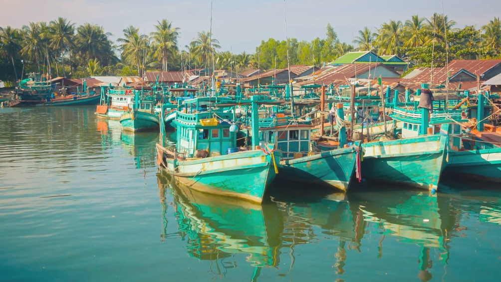 Show item 5 of 5. Green boats in the water in Sihanoukville