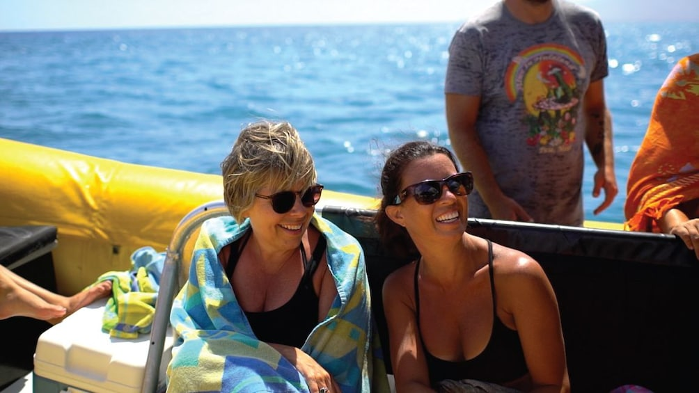 Show item 5 of 10. Two women sit and smile on a boat in Hawaii