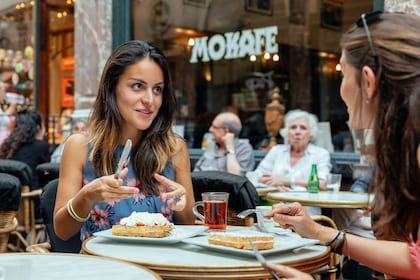 Two women eat Waffles at an outdoor cafe patio in Brussels
