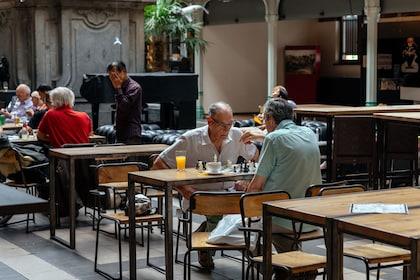 Two older men play chess in a cafe in Brussels