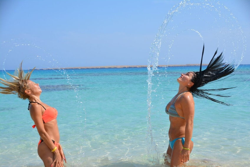Show item 3 of 9. Women whipping their hair back and forth on the beach on Giftun Island