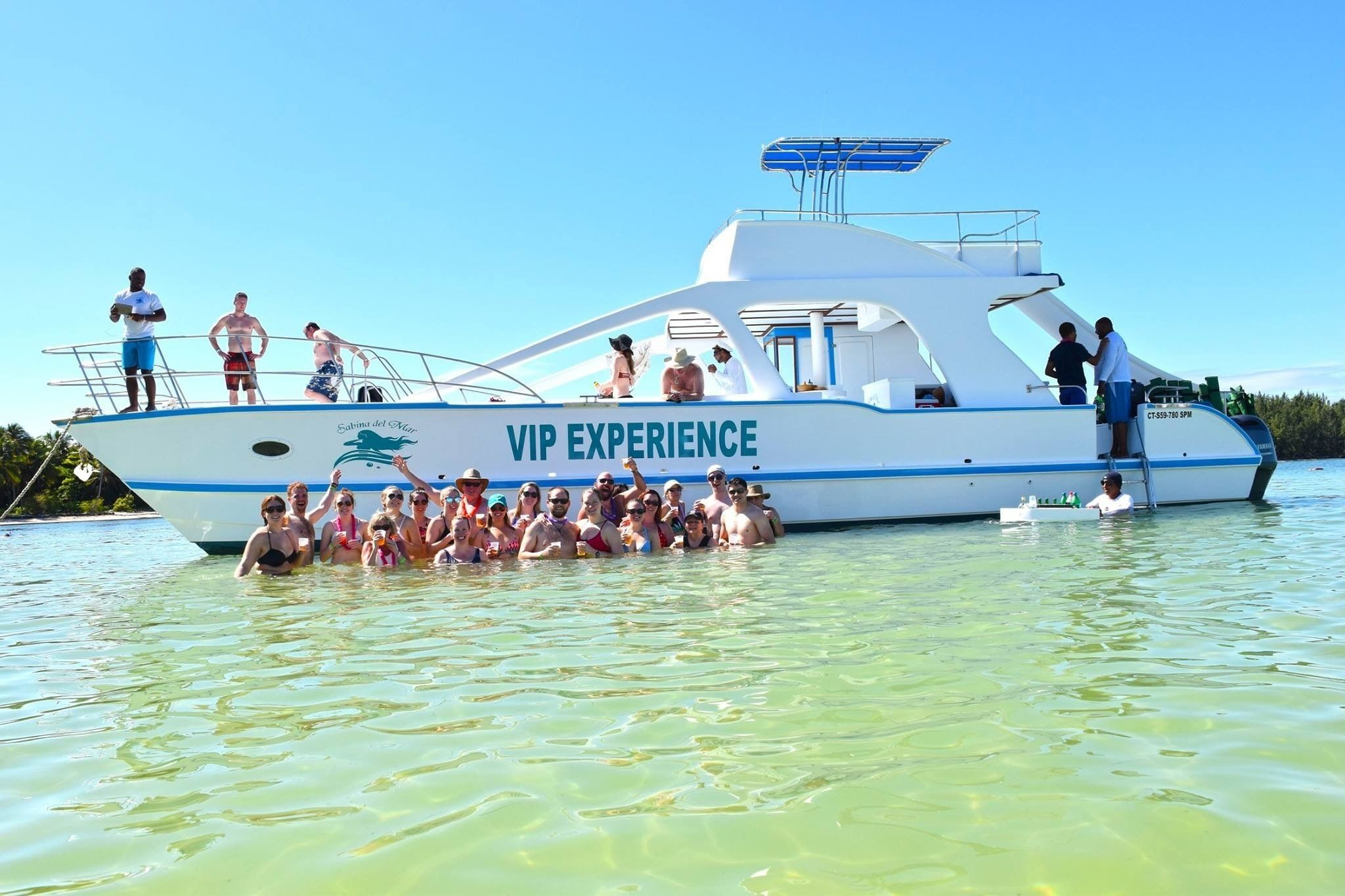 Group standing in the water in front of a catamaran in Punta Cana