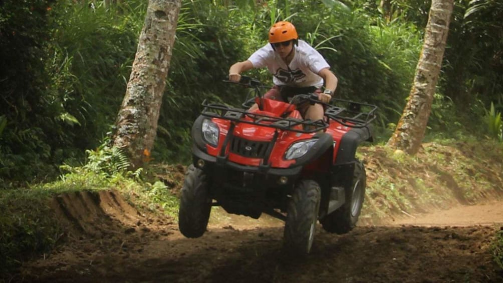 Show item 2 of 9. Man riding an ATV on a dirt path in Bali