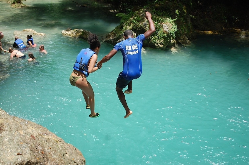 Show item 8 of 8. Couple jumping into the water in Jamaica