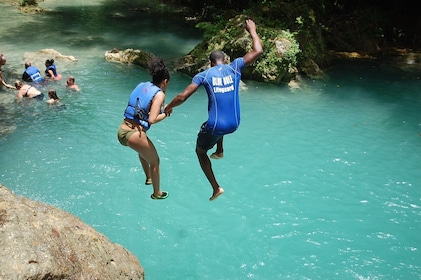 Couple jumping into the water in Jamaica