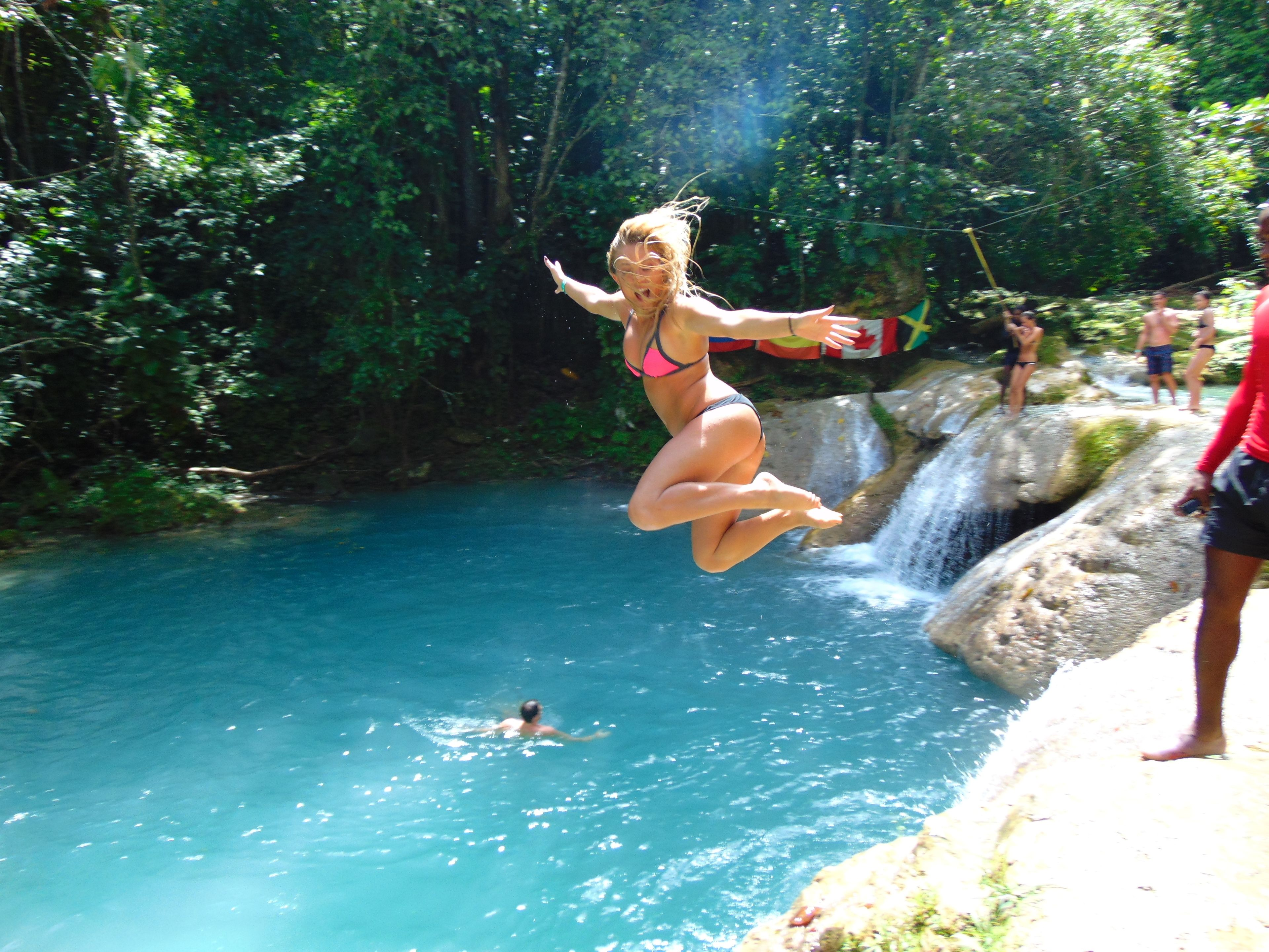 Woman jumping into the water in Jamaica