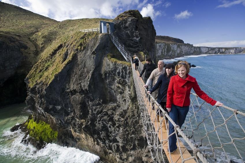 Tourists walk across the rope bridge at the Giants Causeway
