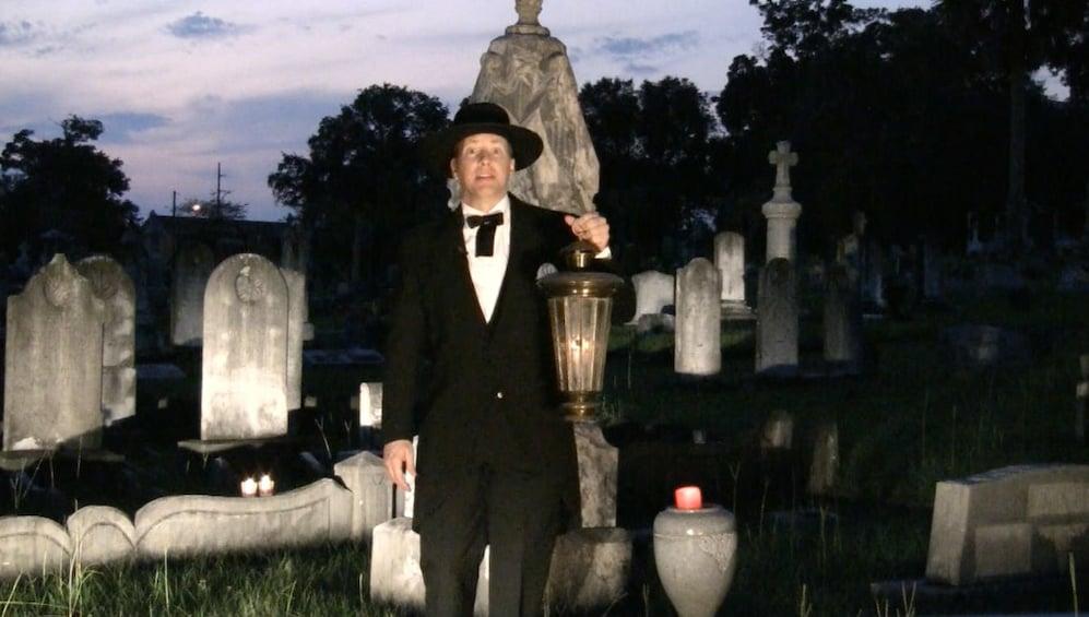 Show item 1 of 3. Tour guide walking through historical St. John's Cemetery in Pensacola, Florida
