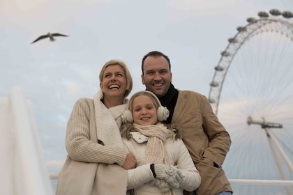 Family on a River Thames cruise with the London Eye in the background