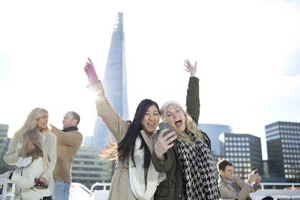 Women taking a selfie from a boat on the River Thames with The Shard in the background in London