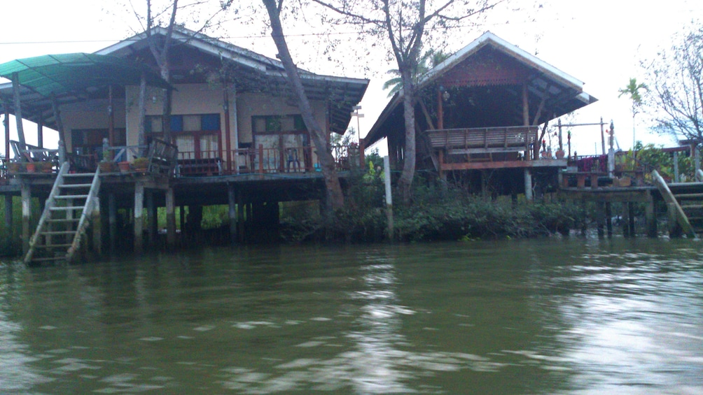 Show item 3 of 11. Two houses on the banks of a river in Maeklong