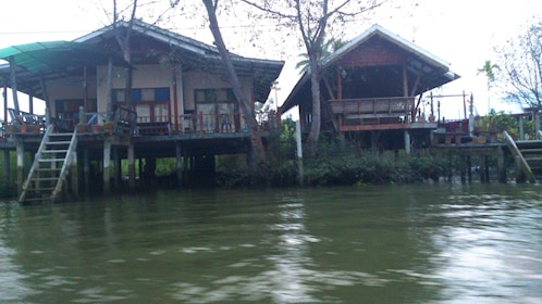 Two houses on the banks of a river in Maeklong