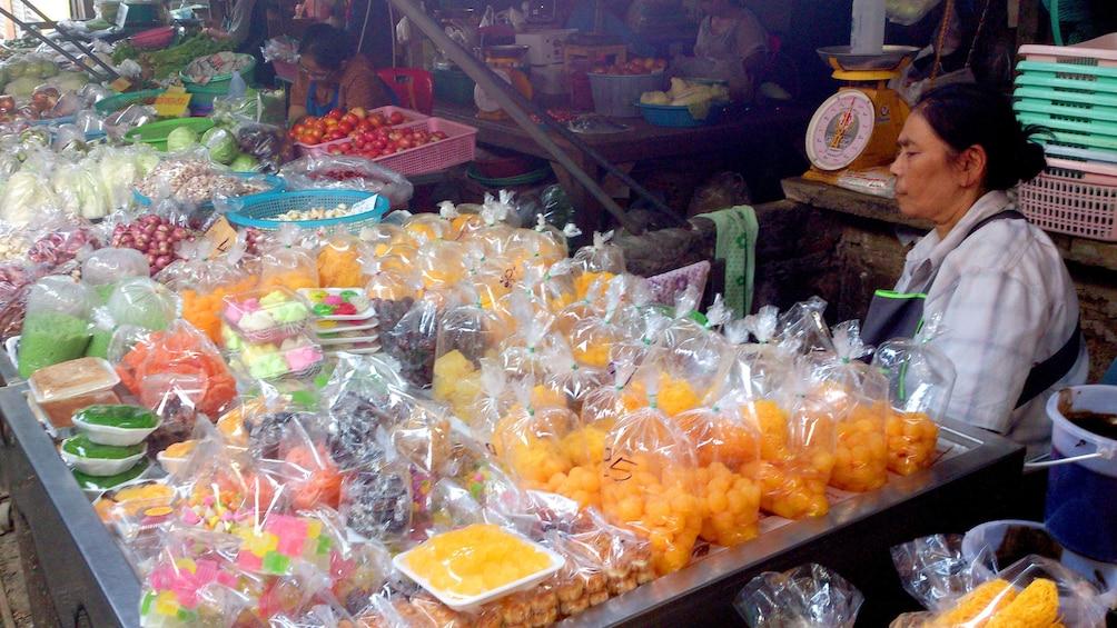 Show item 5 of 11. Woman sells candy goods at the Maeklong Risky Market