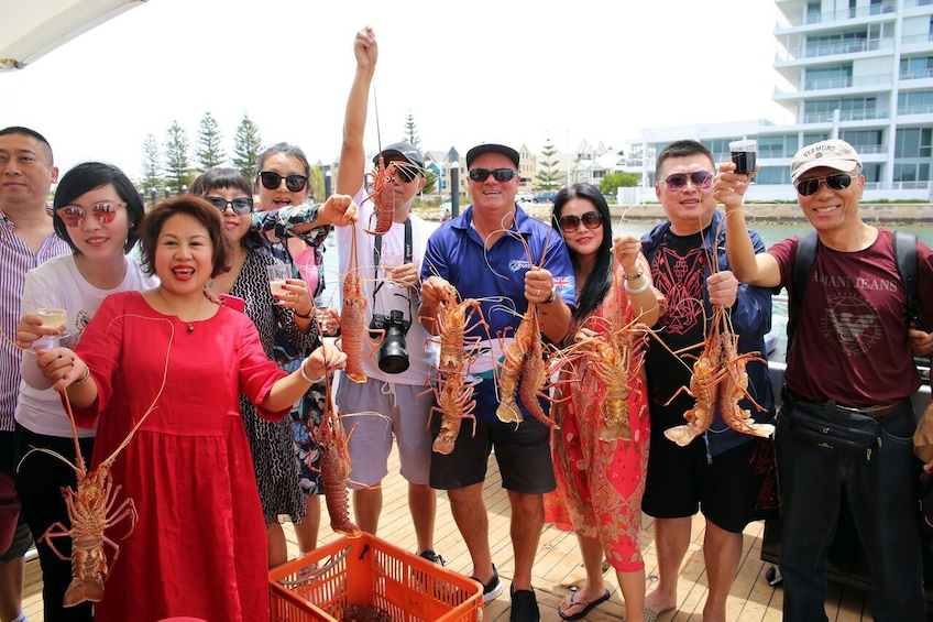 Show item 1 of 6. Group holding up lobsters in Australia