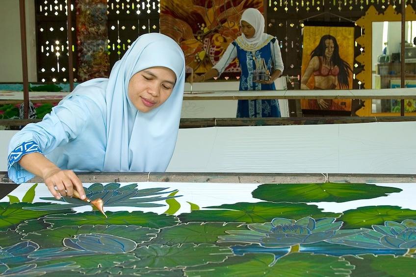Show item 10 of 10. Traditional batik printing process using wax and dye at the Atma Alam Batik Art Village