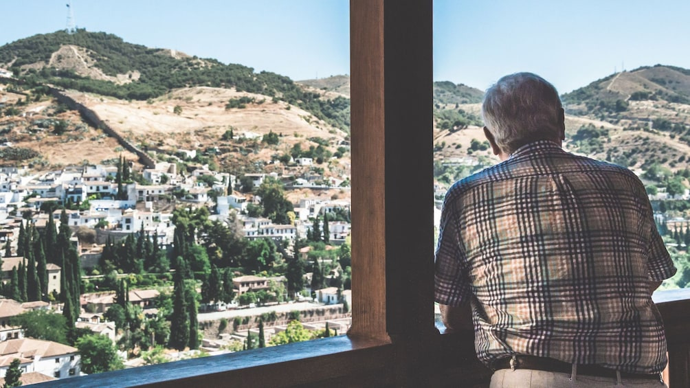 Show item 2 of 10. Man looking out at a view from Alhambra Palace in Granada