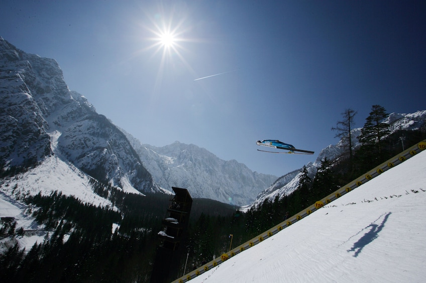 Show item 3 of 7. Person skis on the long jump in the Alps