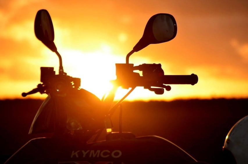 Show item 6 of 6. Sunset shows silhouette of ATV handles and mirrors