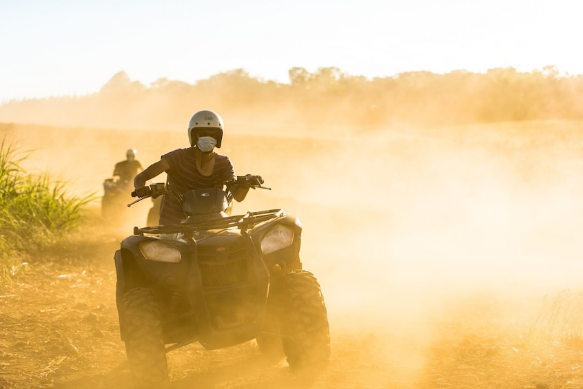 Show item 1 of 6. Man with mask rides an ATV through dusty Mauritius landscape