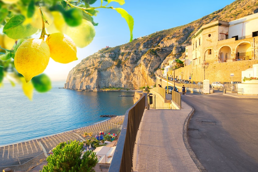 Show item 2 of 10. View of Amalfi coast on a sunny day with a lemon tree in the foreground