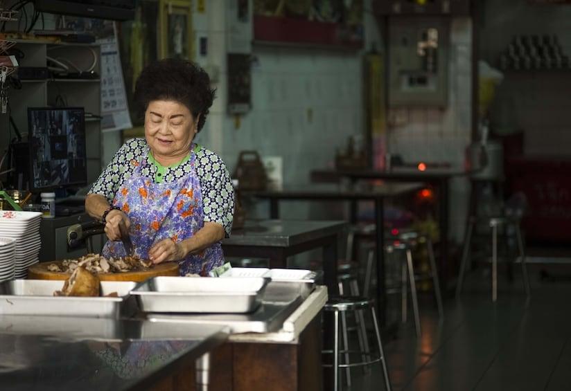 Show item 5 of 10. Woman preparing food in Bangkok