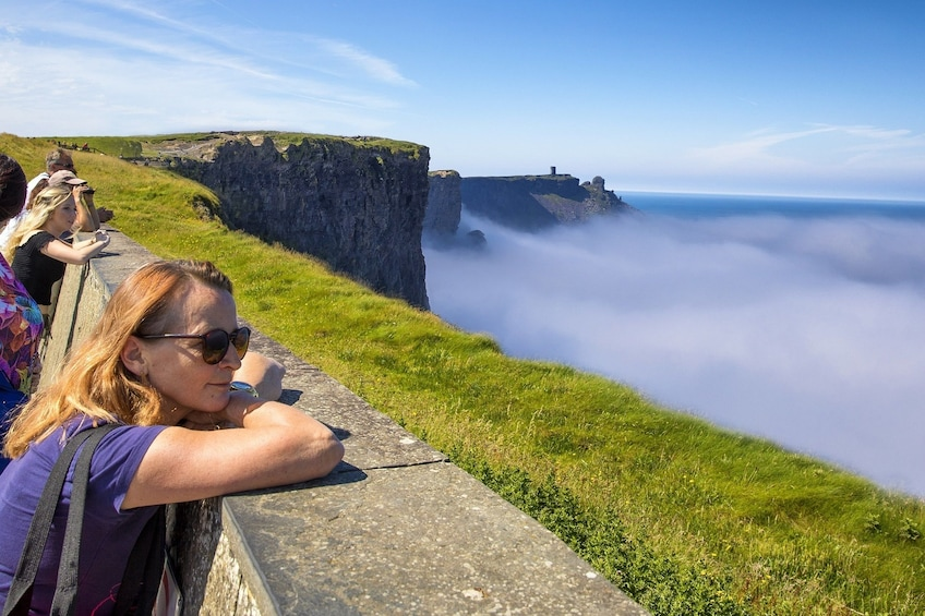 Show item 5 of 9. Woman leans on ledge at Cliffs of Moher