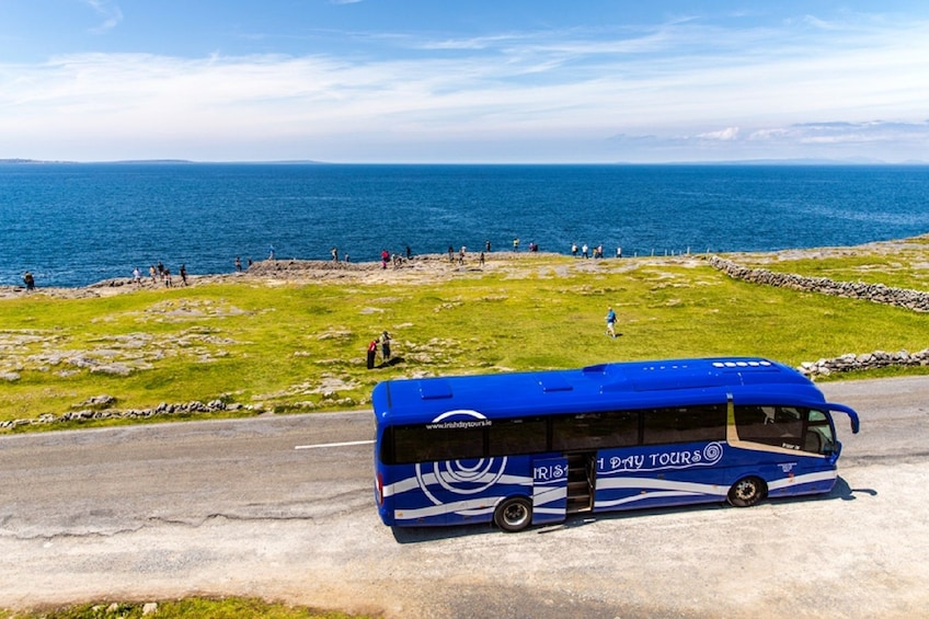 Show item 4 of 9. Blue bus passes the Cliffs of Moher