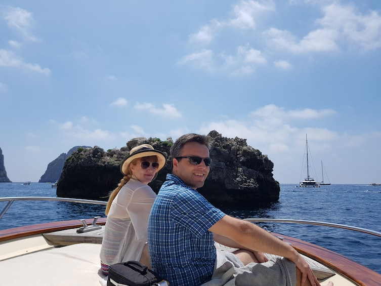 Show item 5 of 10. Two tourists sit on boat with sea in the background