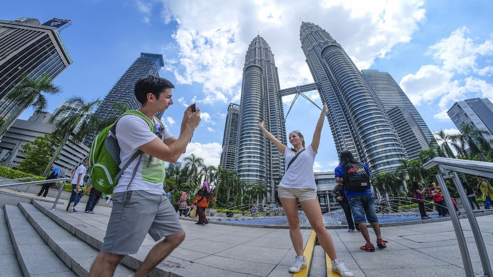 Show item 1 of 4. Tourists take photo in front of Petronas Twin Towers