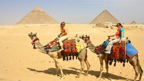Tourists ride camels past the Pyramids of Giza