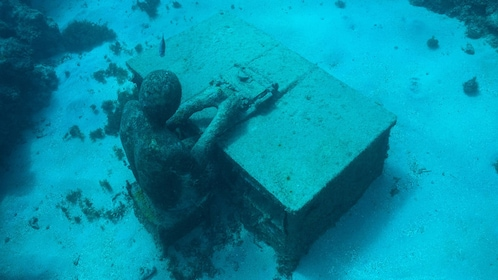 Underwater sculpture of person at a desk typing a typewriter