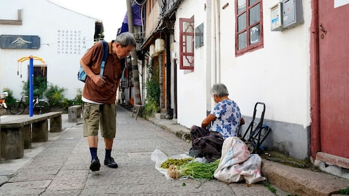 Local woman selling produce on the side of the road in Fengjing