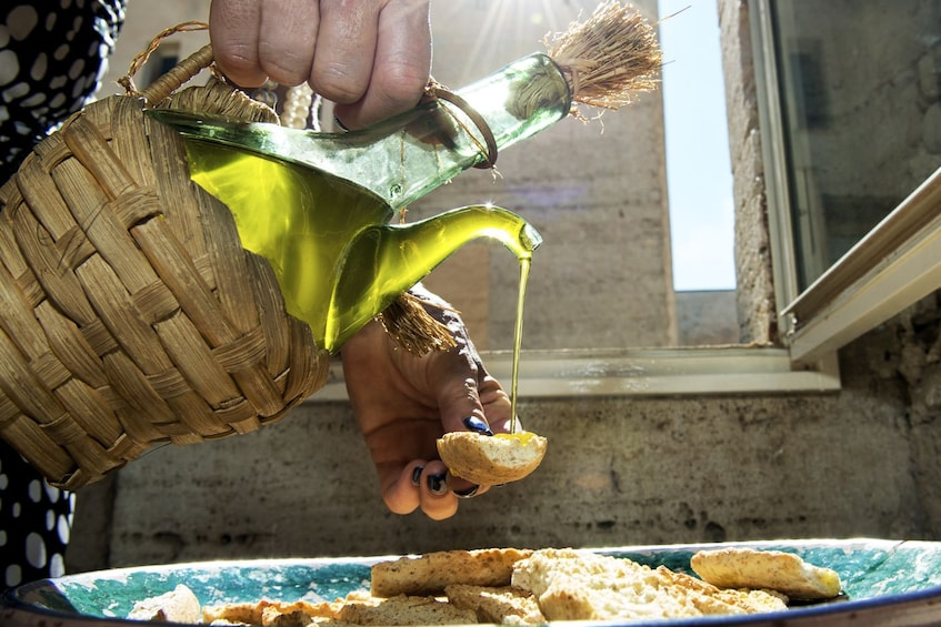 Show item 1 of 8. Woman pouring olive oil on bread in Cagliari