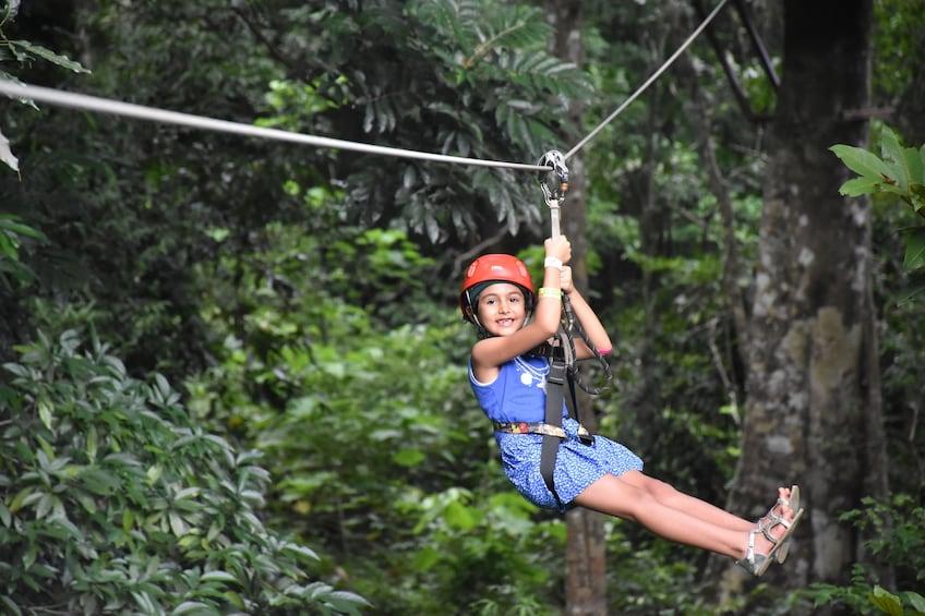 Show item 3 of 9. Young girl ziplining on Langkawi Island