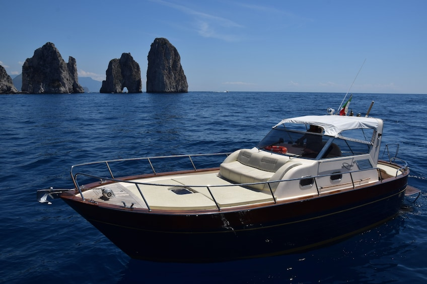 Show item 3 of 10. Small boat in water with islands of Capri in the background