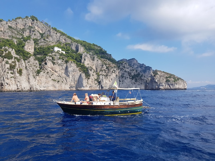 Show item 5 of 5. Small boat approaching coast of Capri, Italy